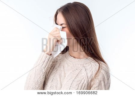 girl in the sweater keeps near the nose Hanky isolated on white background