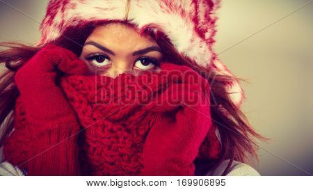 Winter clothing fashion concept. Closeup of young mulatto woman covering her face with hands wearing gloves and scarf. Mixed race girl in wintertime clothes fur cap studio shot