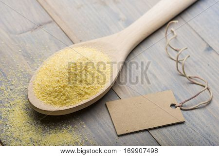heap of yellow flour in wooden spoon on table with label for text.