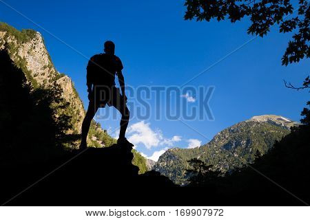 Looking at view at edge of the canyon. Success and achievement silhouette hiking or climbing man with backpack celebrating beautiful inspirational landscape. Samaria Gorge canyon in Crete Greece.
