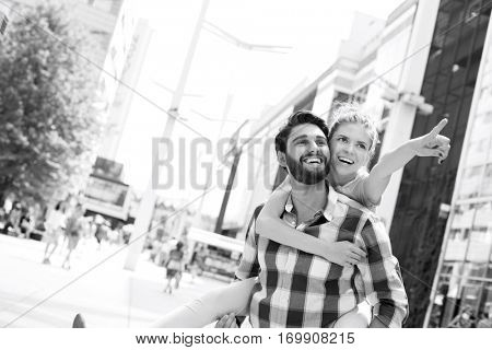 Happy woman showing something to man while enjoying piggyback ride in city