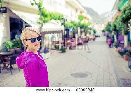 Young girl with sunglasses walking on city street on vacations. Travel and tourism in beautiful places on Crete Greece.