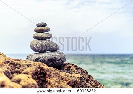 Stones balance and wellness retro spa concept inspiration zen-like and well being tranquil composition. Close-up of white pebbles stack over blue sea
