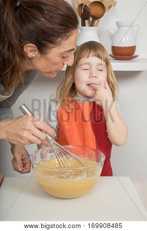 Child Tasting Whipped Cream Next To Mother