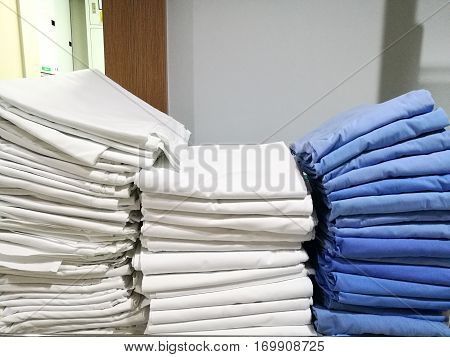 pile of white and blue cloth towel bedspread bedsheet in the hospital with blur white wall background