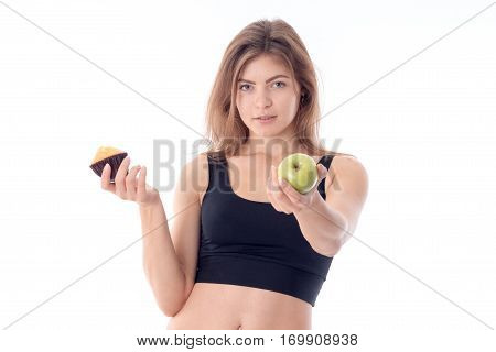 fitness girl stretches forth his hand with an Apple and a second hand keeps the fruitcake