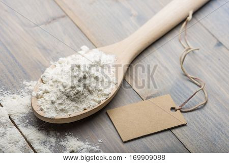 heap of white flour in wooden spoon on table with label for text.