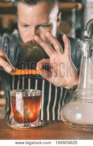 Handsome barman is making cocktail at night club. Unique man. Bartender has a mustache and stylish hairstyle