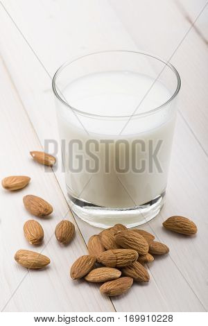 glass of milk with almonds on wooden table