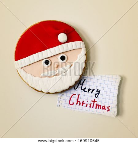 high-angle shot of a christmas biscuit in the shape of the face of Santa Claus on an off-white surface and a piece of paper with the text merry christmas handwritten in it