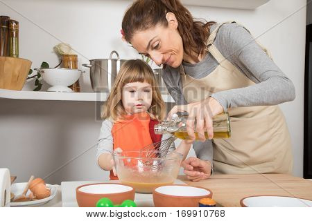 Woman And Child Cooking Pouring Oil In Bowl