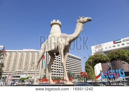DUBAI UAE - DEC 6 2016: Camel statue with a tower at the Dubai Creek in Deira. Dubai United Arab Emirates Middle East