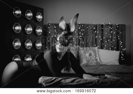 Seductive woman in black leather rabbit mask posing on a bed