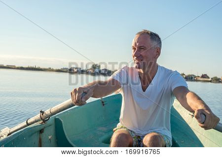 Happy Man Is Rowing On A Small Boat