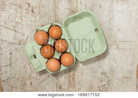 Eggs In A Carton On A Wooden Surface