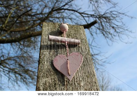 Pink wooden heart with pink sisal Cordel in the midday sun in Häselingen in February 2017, in the background a brown-gray weathered Wooden post , In the background branches of a tree and bright blue sky.