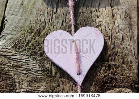 Pink wooden heart on pink sisal Cordel to the midday sun in Häselingen in February 2017, in the background a brown weathered wooden fence .