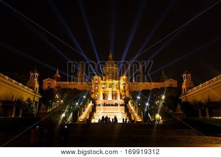 Large group of people looks at the musical fountain of Montjuic near the National Art Museum of Catalonia at night