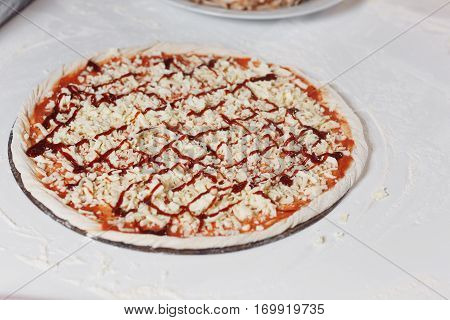 Cooking pizza. the workpiece poured tomato sauce. Closeup cook at kitchen