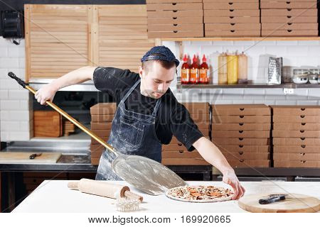 Raw pizza ready to bake. Cook in a blue apron in the kitchen. with a shovel in his hands. boxes for food delivery on background