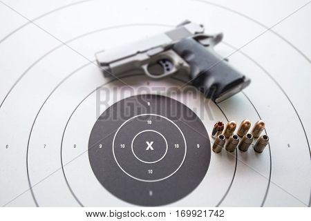 11 mm or .45 bullets on bullseye target with blurred pistol gun and copy space