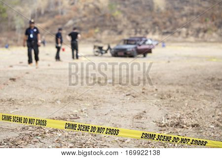 police line tape and blurred law enforcement searching wrecked car background with copy space