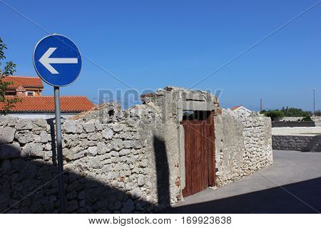 Southern town street with old stone fence and road sign. Ancient stone wall with small wooden door. Road sign in the village street.