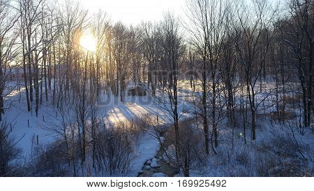Morning view of a Snow covered valley with a creek and shed at sunrise