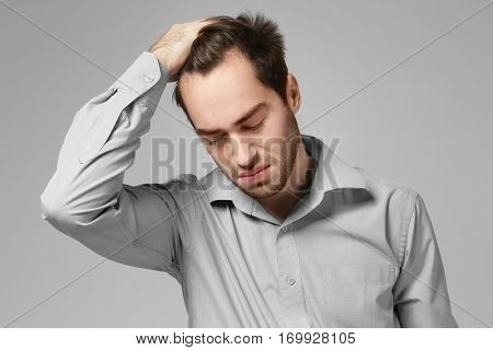 Depressed young man on grey background
