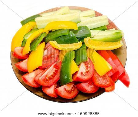 Transparent plate with sliced red tomatoes yellow and green capsicums and cucumbers
