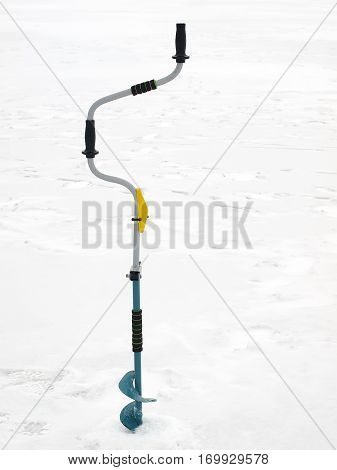 Small hand operated ice auger used in ice fishing on a background of snow and ice.