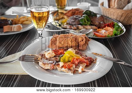 ChicSkewers of chicken and Turkey meat in batter with tomatoes, green peppers , tomato sauce and mayonnaise on a white plate, a fork, a knife, a glass of beerken skewers with vegetables on white plate