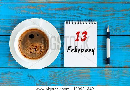 February 13th. Day 13 of month, Top view on calendar and morning coffee cup at workplace background. Winter time.