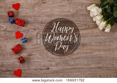 White roses with hearts on wood background. Love design. Happy Womens day, 8 march concept. Fresh natural flowers with gift boxes. Wooden rustic board.