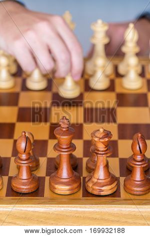 Hand With Pawn Makes First Move On Chess Board