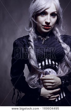 Scary old-fashioned girl with black eyes posing over grey background
