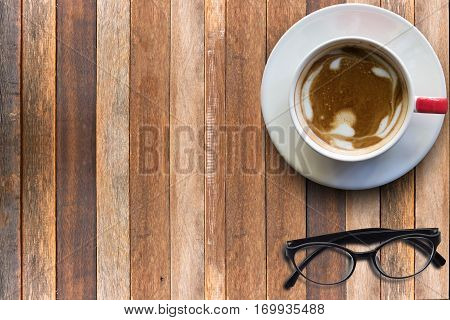 Hot cappuchino and eyeglasses on wooden textured background