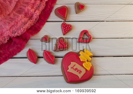 St. Valentines composition. Top view on red glazed honey cakes in shape of heart lips with word love lay on white wooden table near rose lace