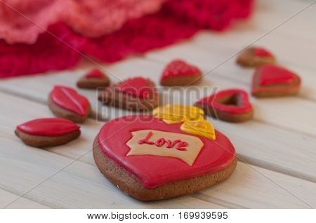 St. Valentines composition. Red glazed honey cakes in shape of heart lips lay on white wooden table near rose lace. Focus on word love