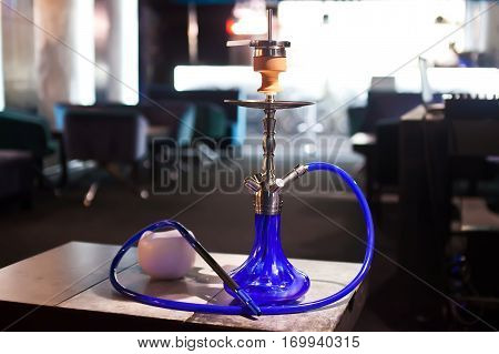 Close-up photo of blue hookah with tube.
