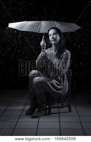 Beautiful woman with silver dress sitting in rain under an umbrella at night