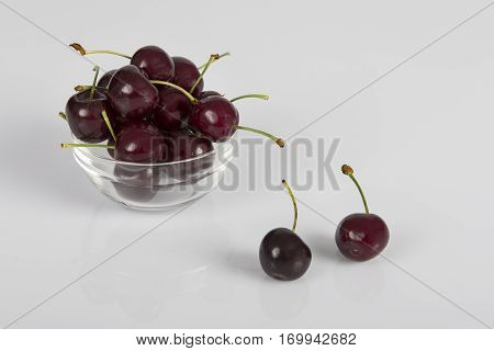 Close-up of cherries in glass bowl on a white background