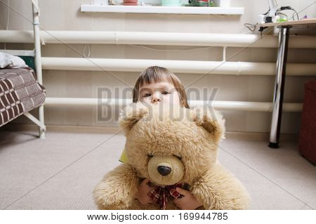 child hugging teddy bear indoor in her room devotion concept kid hiding behind the toy