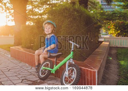 Active Blond Kid Boy Driving Bicycle In The Park Near The Sea. Toddler Child Dreaming And Having Fun