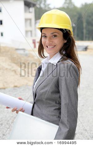 Businessman with helmet checking site under construction