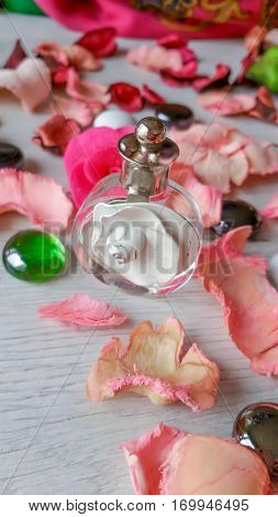 Vintage perfume bottle with a delicate pink fragrance and rose petals