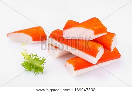 Crab sticks with lettuce on White. Studio Photo