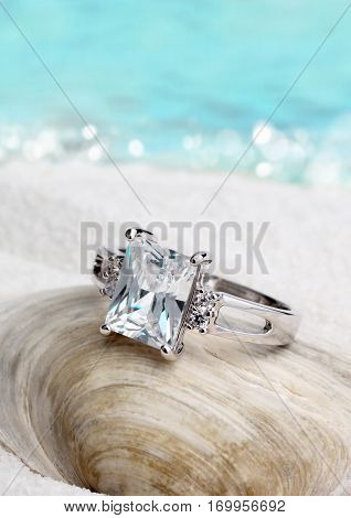 Jewelry ring with diamond on sand beach background soft focus