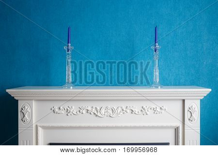 Two crystal candlestick with blue candles standing on a white fireplace