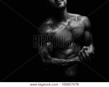 Strong athletic man cropped portrait. Handsome male fitness model showing naked torso, muscular body. Strong muscles and biceps. Studio shot, black and white. Bodybuilding concept